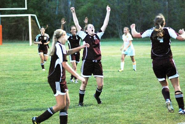 Charlevoix senior midfielder Megan Peters (middle) celebrates moments following the end of the second overtime as the Rayders clinched the Lake Michigan Conference title Thursday at Ottawa Stadium in Harbor Springs. The Rayers went on to defeated the Rams, 3-2, in a shootout.