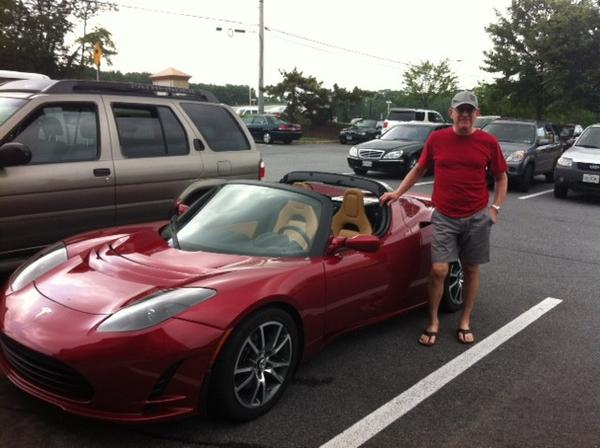 John Skouge, a skin cancer surgeon, poses with his Tesla roadster in a Starbucks parking lot in Timonium.