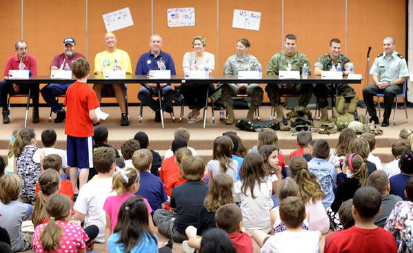 A third grade Steckel student asks a question of the panel of service members Friday. Service members are, from left: Joe Busch of Whitehall (Army); Joe Novajovsky of Whitehall (Air Force); Scott Brown of Whitehall (Army); Richard Kichline of Allentown (Navy); Denisse Rivera of Whitehall (Army); Nicole Hughes of Whitehall (Army); Sam Willard of Chesapeake, Va. (Navy); Charles Manula of Virginia Beach, Va. (Navy) and Robert Munden of Chesapeake, Va. (Army).    Third-graders at Steckel Elementary brought in members of the armed services to talk about their wartime experiences in an assembly Friday.