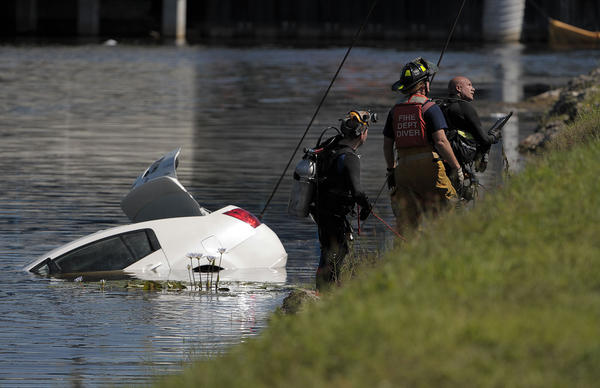 Plantation Fire Rescue Dive Team members hook up their cables to a white Nissan Altima that was found in a canal along Old Hiatus Road. Two bodies were found inside the car.