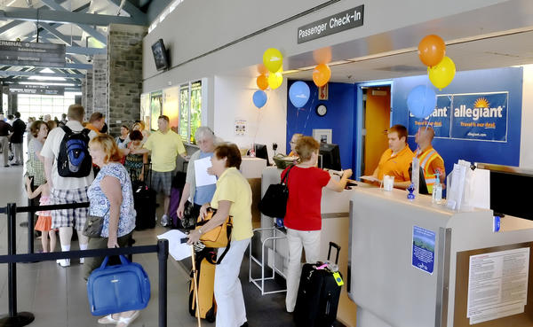 People line up at the Allegiant ticket counter on Friday for a flight to Orlando area.
