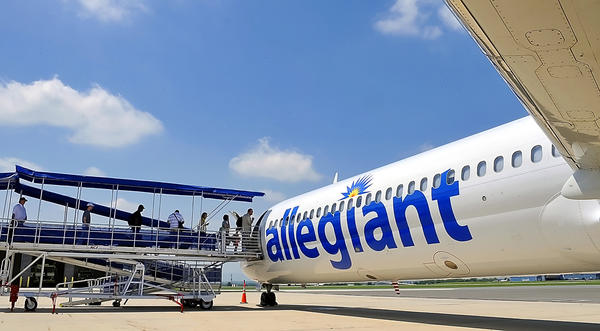 People board a Allegiant MD-80 on Friday for a flight to Orlando area.