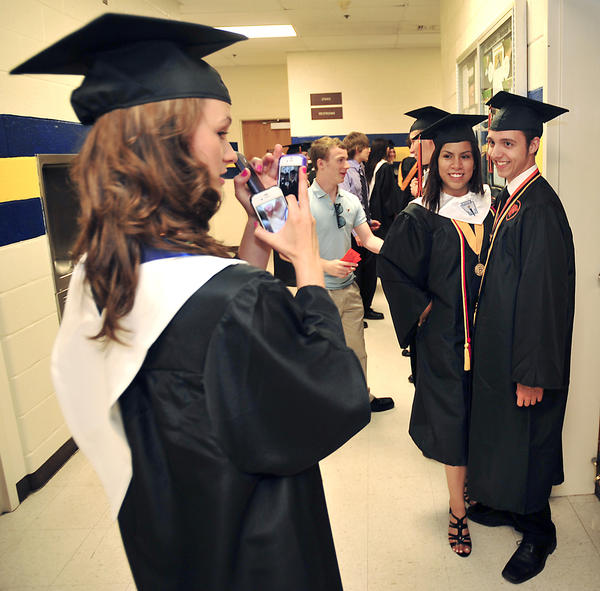 Brittany Rimmer, left, takes a picture of fellow graduates Kenny Romero and Tony Riner just before commencement ceremonies for Martinsburg High School at Shepherd University's Butcher Athletic Center on Friday.