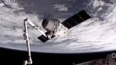 This image provided by NASA-TV shows the SpaceX Dragon commercial cargo craft, top, after Dragon was grappled by the Canadarm2 robotic arm and connected to the International Space Station, Friday, May 25, 2012. Dragon is scheduled to spend about a week docked with the station before returning to Earth on May 31 for retrieval.