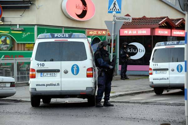 Police officers stand guard on a street after a man opened fire in Hyvinkaa.