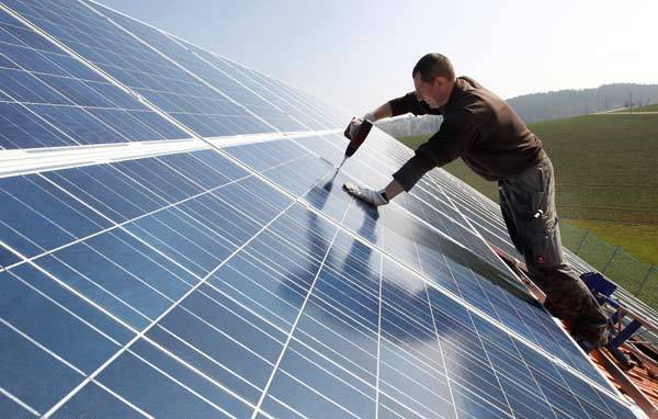 A worker mounts 320 square meters of solar panels on the roof of a farmstead barn in Germany.