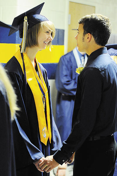 Hedgesville High School graduate Maddy Crawford, left, meets with her boyfriend Joe Gentile, right, minutes prior to walking into commencement Saturday morning at Shepherd University's Butcher Center. Gentile was serving as a junior escort for commencement.