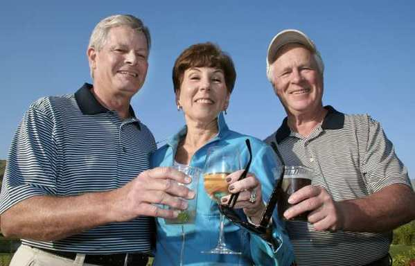 Ready to try for a 'Shot-at-a-Million' at the Hathaway-Sycamores Golf Classic are, from left, golf twosome Mike Malone and Charles Kenney. Mikes wife Cynthia Malone joins the toast.