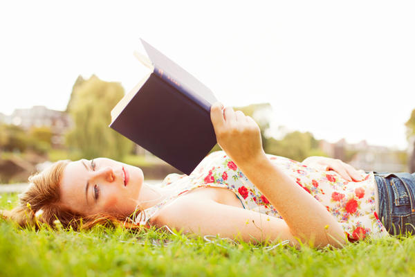 Young woman on grass reading book.