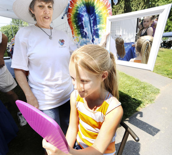 Linda Bonskowski holds a mirror so that Kenedy Gardenhour can see the brand-new hair wrap she purchased Saturday at Halfway Park Days.