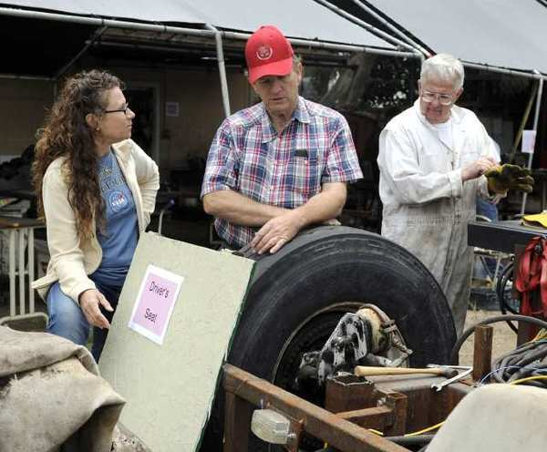 Volunteers Arlene Buchmann, left, Larry Andreason, center, and Chuck Hughes, right look at the float during a community open house hosted by the La Canada Flintridge Tournament of Roses as a part of the Fiesta Days events.