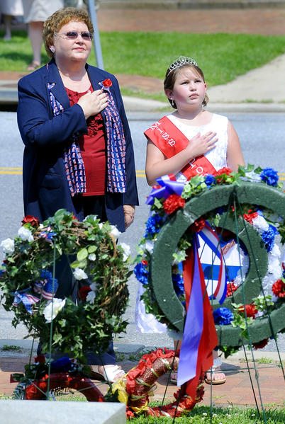Marilyn Hembrock, left, President of Morris Frock American Legion Unit 42 in Hagerstown and her nine-year-old granddaughter Marleigh Toscano rest their hands on their heart after laying a wreath Saturday morning in downtown Sharpsburg.