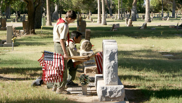 Boy Scouts from Troop 4076 place flags at the gravesites of veterans Saturday in Evergreen Cemetery, El Centro.