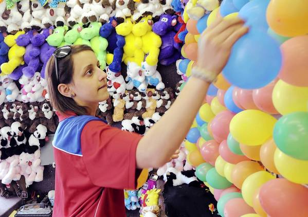 Fullerton Memorial Fair kicks off Thursday, May 30 at Fullerton Memorial Park. Rachel Ricglane, of Allentown, replaces popped balloons in a dart game during last year's event.