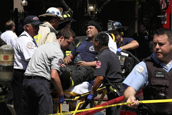 A firefighter suffering from heat exhaustion is taken away on a stretcher after a 3-11 alarm fire which injured 15 at an apartment building on the 6100 block of North Kenmore Avenue in Chicago on Sunday.