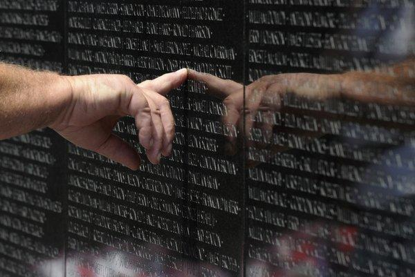 A visitor to the Vietnam Veteran's Memorial touches the name of a fallen soldier etched on the wall of the memorial in Washington, Friday. On Monday, the Vietnam Veterans Memorial Wall will begin the national commemoration of the Vietnam War's 50th anniversary.