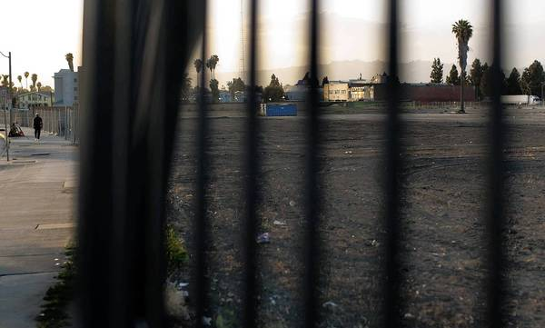 A fence borders most of a vacant lot slated for redevelopment in South Los Angeles at the corner of Marlton Avenue and Santa Rosalia Drive. The 22-acre project known as Marlton Square was identified by city officials two decades ago as a prime site for redevelopment.