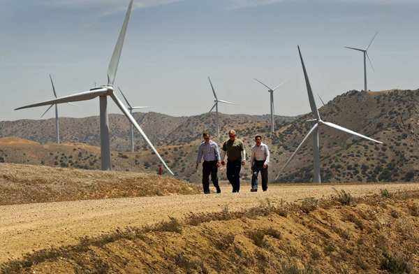 Mark Sedlacek, left, Chuck Holloway and Ken Silver of the Los Angeles Department of Water and Power walk among the wind turbines at the Pine Tree wind farm in the Tehachapi Mountains. Wind energy farms are being approved across ridgelines used by endangered condors and federally protected eagles. Recently, renewable energy companies and federal biologists have been trying to develop technologies to prevent those birds and others from colliding with the turbine blades.