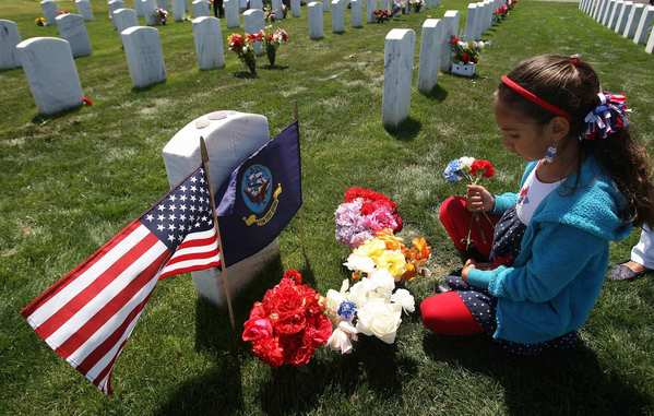 Jackelynn Freund, 8, of San Diego adds flowers -- some of them picked from her garden -- to the flag-bedecked headstone of her grandmother, Navy veteran Jessie Coats, during the Memorial Day ceremony at the new Miramar National Cemetery in San Diego.