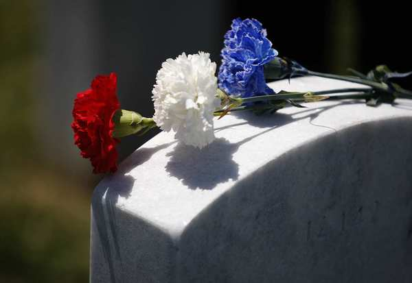Red, white and blue flowers are placed on the gravestone of Robert Worden, who served in the Marines during the Korean War, during the inaugural Memorial Day ceremony at the new Miramar National Cemetery in San Diego.