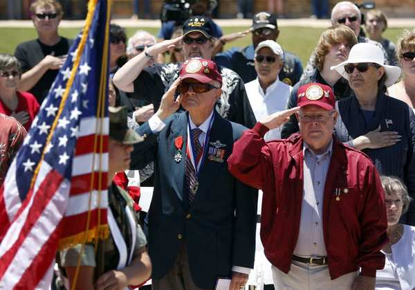 William Brooks, 91, center, a World War II veteran who survived a prisoner of war camp in Germany, and Tom Crosby, 78, right, a Navy WWII veteran who survived three years in a Japanese POW camp, salute as the San Diego Young Marines present the colors during the inaugural Memorial Day ceremony at the new Miramar National Cemetery in San Diego.