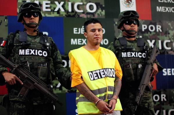 "Mexican soldiers flank Daniel ""El Loco"" Ramirez during his presentation to the news media in Mexico City this month. Ramirez is believed to be a member of the Zetas drug cartel, which authorities suspect of dumping 49 mutilated bodies near Monterrey."