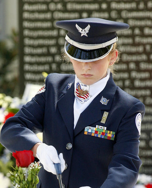 A Crescenta Valley High School ROTC cadet lights a yellow candle on a symbolic table for soldiers missing in action at the City of Glendale's Memorial Day ceremony at City Hall.