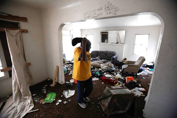 Joe Stringer of the Alliance of Californians for Community Empowerment steps though the garbage-strewn living room of a blighted home in the 11200 block of South New Hampshire Avenue.