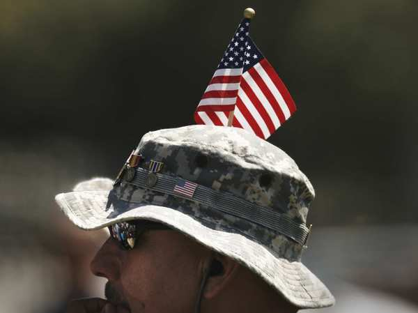 Vietnam War veteran Pete Hernandez listens with a flag in his hat during the Memorial Day observance at Los Angeles National Cemetery in Westwood.