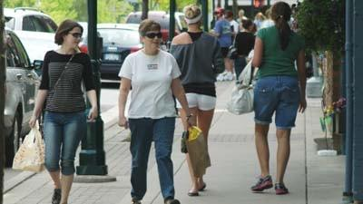 Pedestrians move along a sidewalk Saturday in Petoskey's central business district.