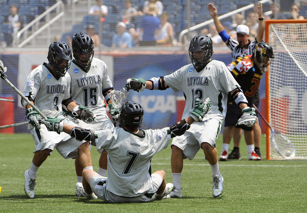 Loyola lacrosse team mates No. 3 Chris Layne, No. 15 Justin Ward and No. 12 Eric Lusby gather around No. 7 Davis Butts after his goal in the first quarter. Loyola defeated Maryland  in Foxboro, Mass., to win the championship.
