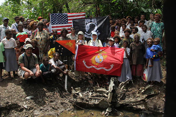 Villagers from the Vudal settlement who helped uncover a U.S. Marine Corsair fighter that crashed in Papua New Guinea in late 1944 gather after markings on the plane were identified. Pilot Lt. Moszek Murray Zanger bailed out but was killed by the Japanese. Zanger's three nieces stand behind the USMC flag (left to right): Andrea Talbutt, Marcy Hanigan and Susan Nishihira. Holding the Papua New Guinea flag is Veline Wesley, who found the Goodyear marking on a fragment that everybody had been searching for. In the rear between Wesley and Talbutt in sunglasses is Henry Sakaida, a Temple City researcher who had discovered for the sisters what had happened to their uncle. Expedition leader Justin Taylan is kneeling in shorts and a hat at front left.
