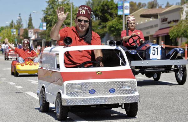 Shriners from the Awesome A Shrine Club wave to the crowd during a Memorial Day parade on Monday, May 28, 2012.