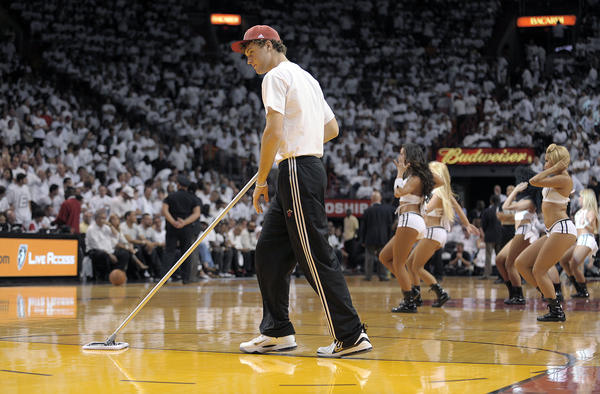 A worker for the Miami Heat wipes down the floor during a timeout of the Heat's Round 3, Game 1 playoff game against the Boston Celtics, Monday, May 28, 2012, at American Airlines Arena.