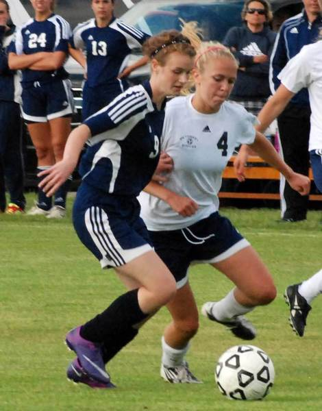 Petoskey junior Morgan Jons (4) and Cadillac sophomore Abbey Fuller chase down a free ball during the first half of Tuesdays Division II district match at the Click Road Soccer Complex.