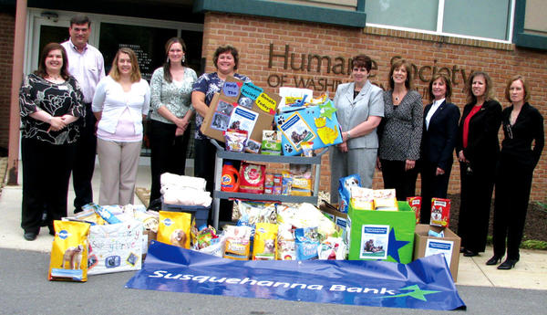 Pet supplies collected by Washington County branches of Susquehanna are displayed in front of the Humane Society of Washington County by, from left, Cindy Helman; Ben Cross, events coordinator for the humane society; Kimberly Hayes; Candace Bageant; Carmen Fox; Melodie Davis; Susan Groe; Kathy Stevens; Tina McDonald; and Katherine Cooker, manager of development and community relations for the humane society.