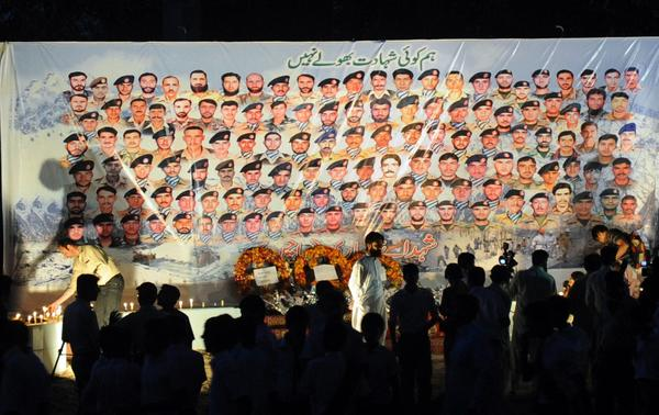 People gather in front of the portraits of Pakistani soldiers victims of an avalanche, during a ceremony in Peshawar on May 30, 2012. Pakistan on May 29, 2012 declared dead 140 people buried alive by a huge avalanche.