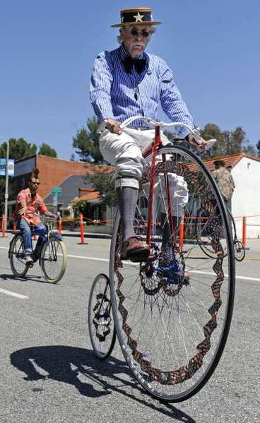 A bicyclist travels down the parade route during the Fiesta Days Parade in honor of Memorial Day on Foothill Boulevard in La Canada.