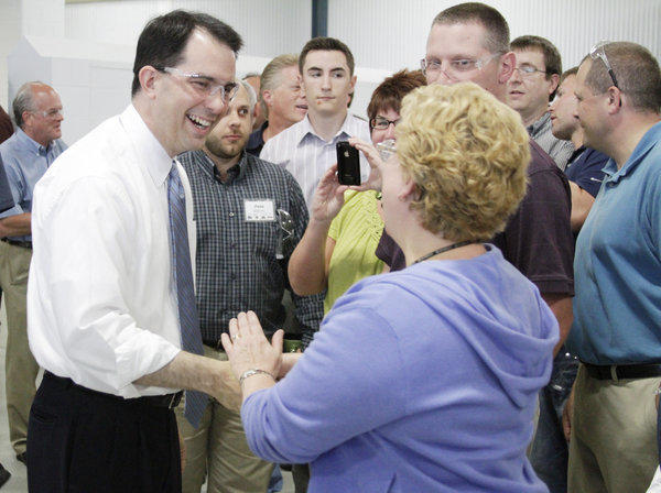 Wisconsin Gov. Scott Walker, who faces a recall election next week, greets Husco International workers in Waukesha. One new poll shows Walker leading his Democratic opponent, Tom Barrett, by 7 percentage points, but another survey shows the race to be in a dead heat.
