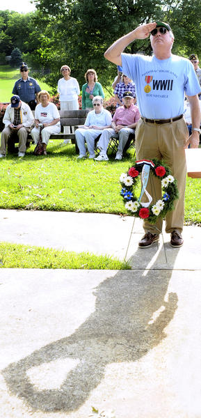 "Chip Zimmer salutes before placing a wreath at the Memorial Day observance ceremony at the Martin ""Marty"" L. Snook Memorial Park Wednesday morning."
