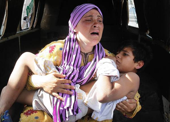 A Syrian woman cries as she carries her son, who was shot in the hand by the Syrian border guard as they were crossing into Lebanon at the Lebanese border town of Wadi Khaled.