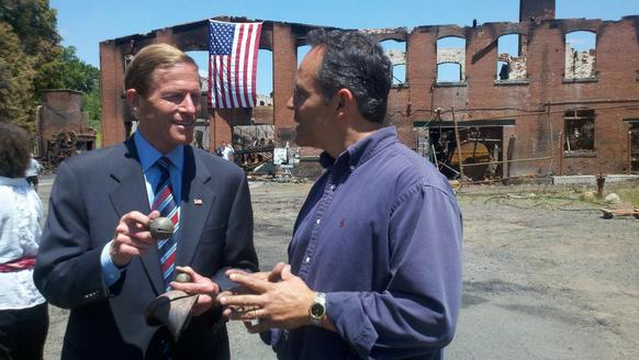U.S. Senator Richard Blumenthal tours the remains of Bevin Bell Mfg. Co. with owner Matt Bevin Thursday. Senator Blumenthal pledged to help rebuild the factory. Blumenthal holds a salvaged Bevin Bell pulled from the ashes.