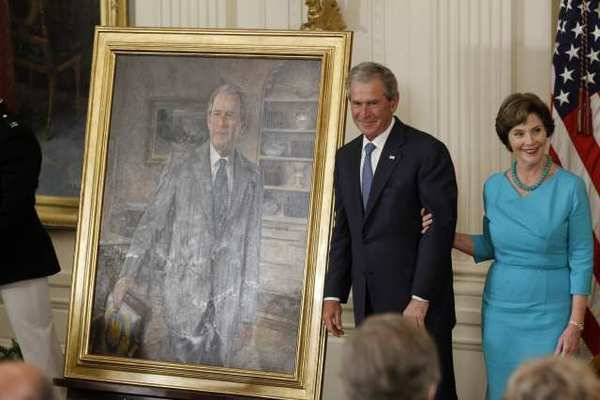 Former President George W. Bush and his wife, Laura, stand next to his portrait during an unveiling ceremony at the White House.