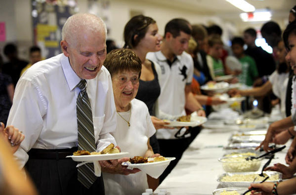 Holocaust survivor Julius Jacobs of Allentown, left, and his wife of 'over 50 years' Rosanna Jacobs serve themselves at a luncheon in Julius's honor held at Northeast Middle School Thursday.     Northeast Middle School, Bethlehem, students hold a Jewish-themed luncheon in honor of Julius Jacobs, who for three years has spoken to students about surviving the Holocaust.