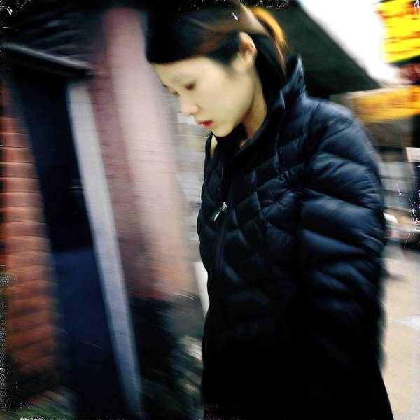 A woman walks along Wentworth Avenue in Chicago's Chinatown neighborhood.