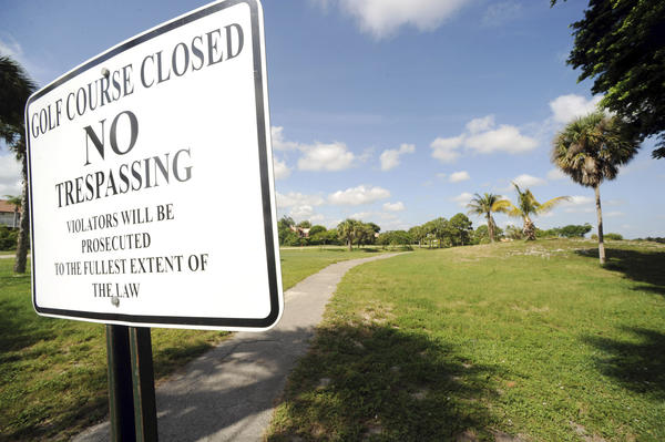 The Florida Department of Environmental Protection contends that owners of a a contaminated portion of the former Mizner Trail golf course west of Boca Raton have yet to follow through with clean-up reporting requirements.