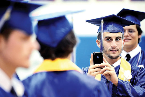 McConnellsburg High School graduate Justin DeShong takes a cellphone photo of classmates before Thursday's graduation services at the high school.
