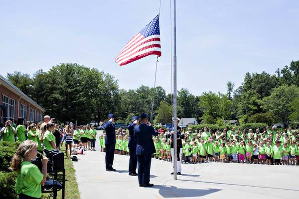 T.C. Walker Elementary School students look on as the flag is lowered during a ceremony Thursday marking the closure of the Gloucester County school.