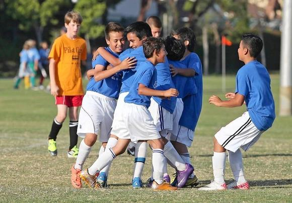 Members of Adams boys' 5-6 silver division team celebrate another goal against Eastbluff.