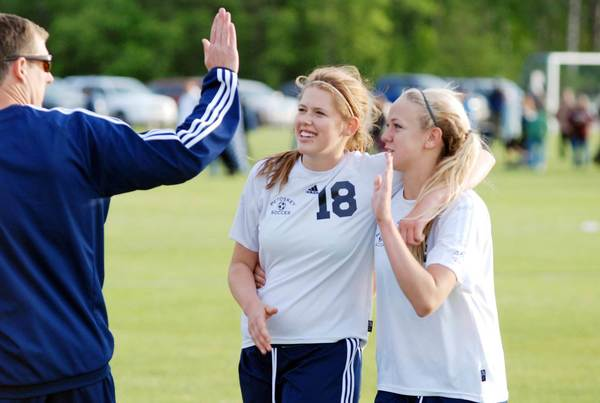 Petoskey senior Quinn Faylor (18) and junior Morgan Jons (right) are congratulated by coach Zach Jonker moments following the Northmen's 1-0 win in a shootout over Gaylord Thursday in a Division II district semifinal match at the Click Road Soccer Complex.